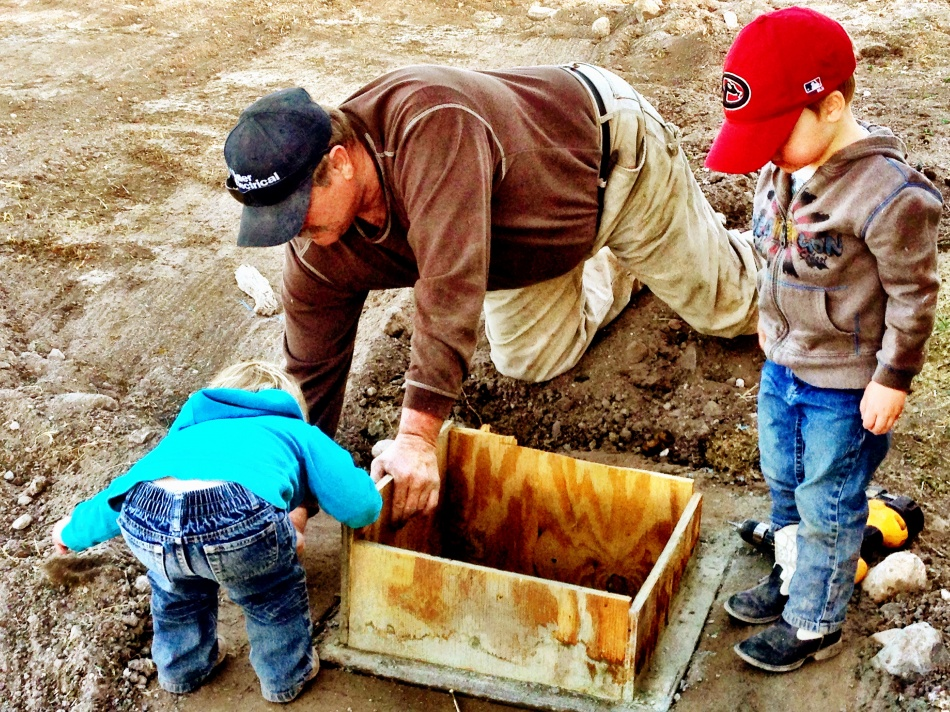 Grandpa's helpers getting the drainage setup around the new barn.